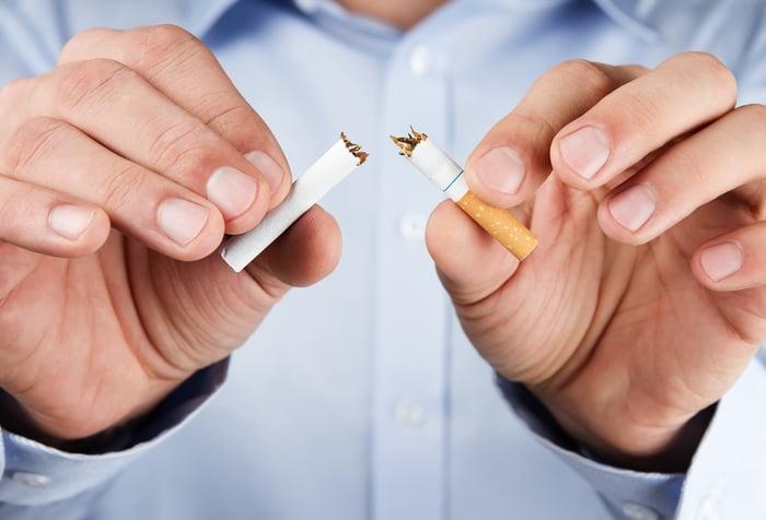 Man breaking a cigarette.