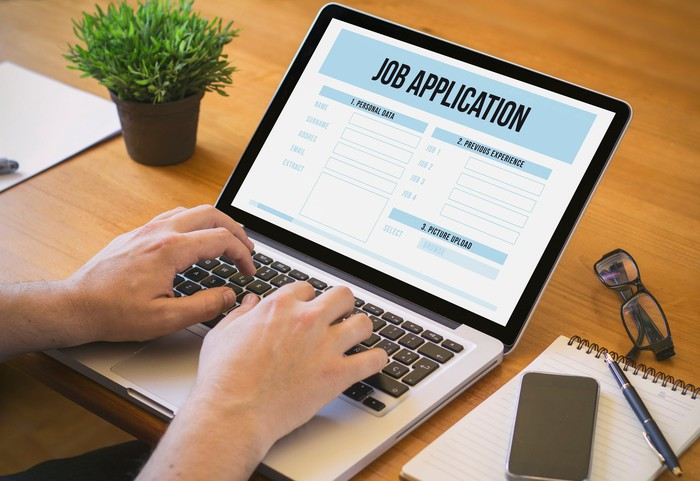 Hands typing on laptop with job application on screen