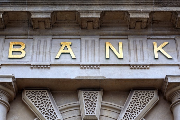 A sign above a bank that says b-a-n-k in gold letters against a limestone backing.