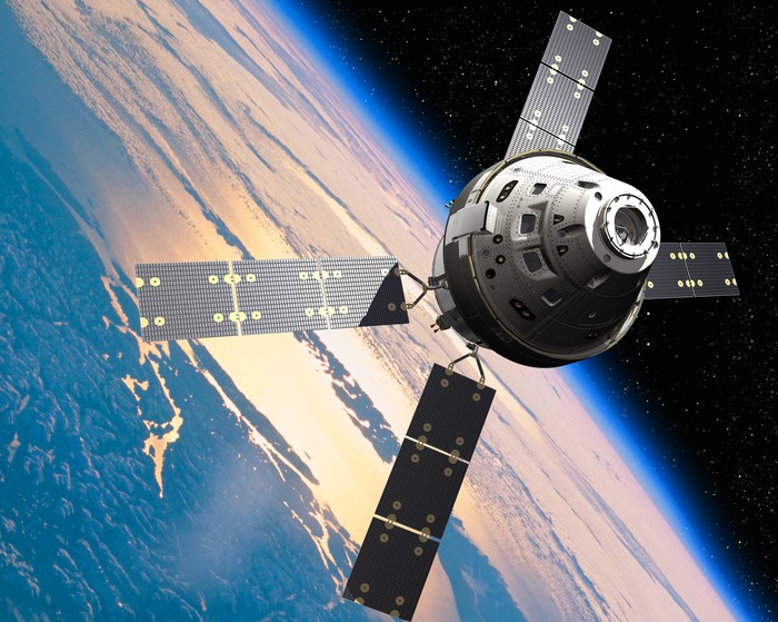 A rendering of the Orion spacecraft over the earth.