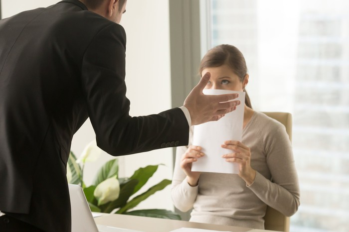Man in suit standing over woman, while she sits and covers her face with a document.