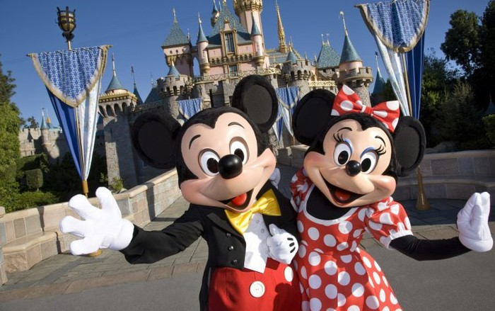 Mickey and Minnie Mouse welcoming guests in front of the Disneyland castle.