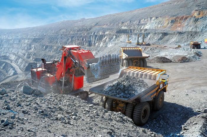 A shovel loader dumping rocks in a big mining truck.