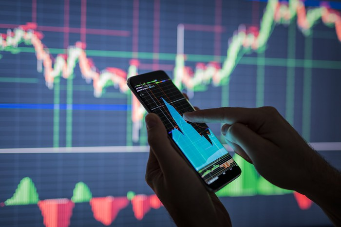 A hand touching a smartphone screen showing a stock chart, with an even bigger stock chart on the wall behind it.