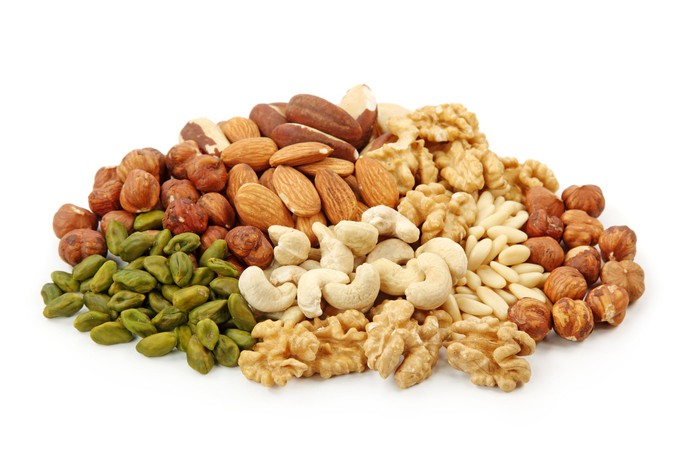A pile of nuts of various types on a white background.