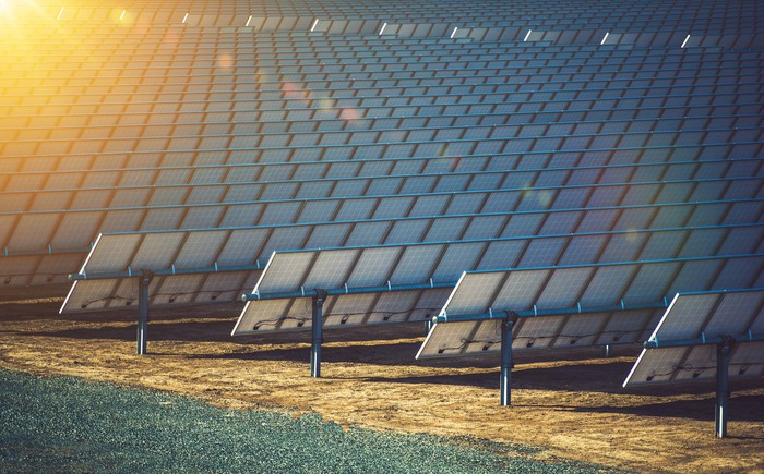 Rows of solar panels with a ray of sunshine in the corner.