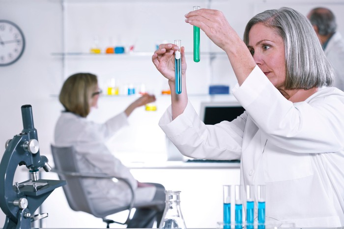 Female scientist holding two test tubes with a microscope and test tube rack nearby and other scientists in the background