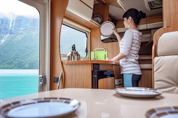 A woman washes dishes in her RV kitchen in view of a mountain lake.