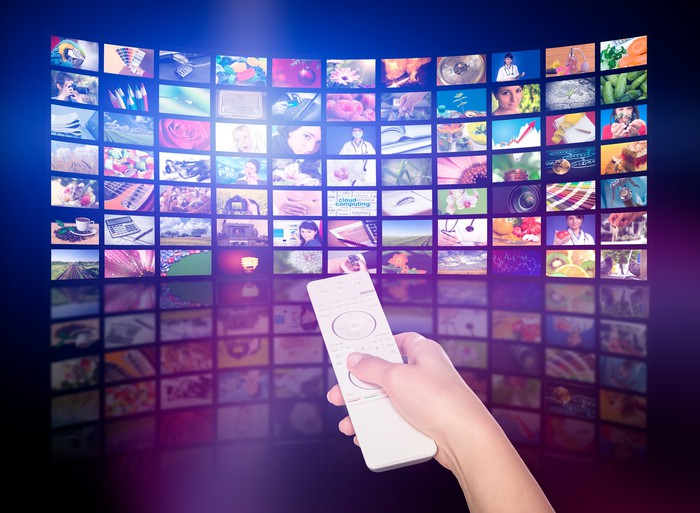 A person points a remote control at a wall of TV screens.