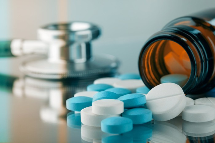 Pills spilling out of a bottle onto a table with a stethoscope in the background