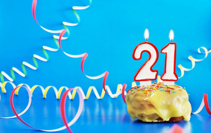 Two lit candles -- a 2 and a 1 -- in a cupcake surrounded by colorful curly paper streamers on a blue background.