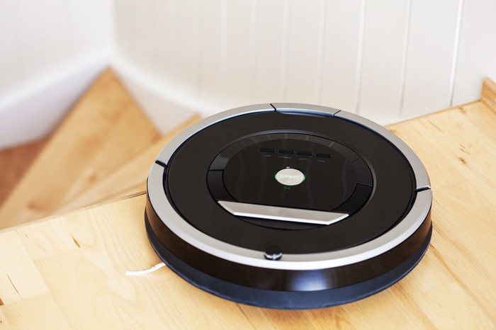 Disc-shaped robot vacuum a the top of a flight of stairs