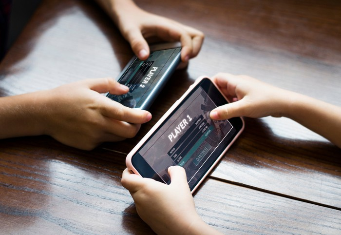 Two pairs of hands across from each other, each holding a smartphone with a game on the screen.