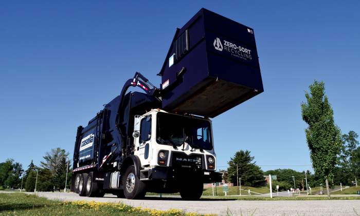 A dump truck lifts a trash container.