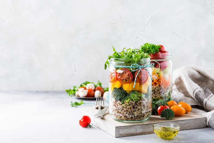 Two mason jars filled with quinoa salad and vegetables.