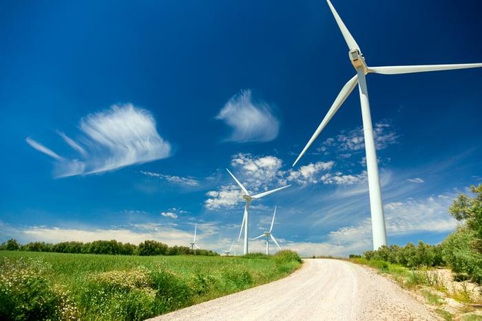 Wind turbines spinning alongside a road.