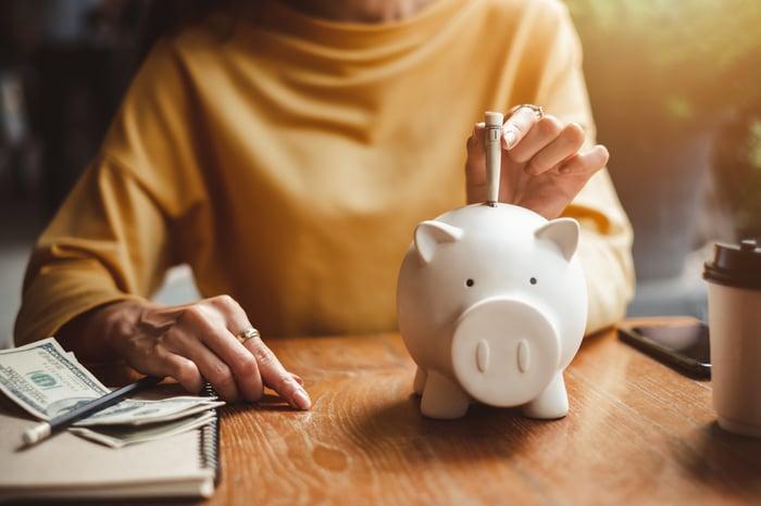 A woman putting cash into a piggy bank.