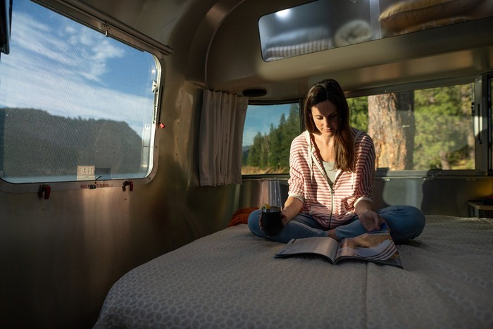 Woman sitting on a bed inside an RV and reading