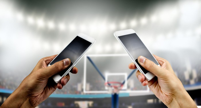 Two different hands, each holding a smartphone, in front of a basketball hoop.