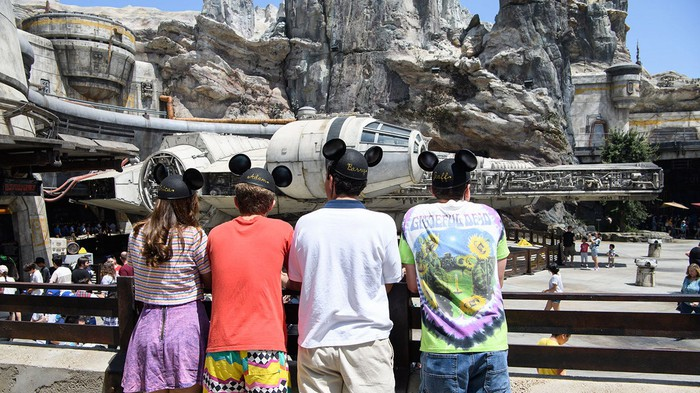 Four young guests wearing Mickey Mouse ears look on at the Star Wars attraction at Disneyland.