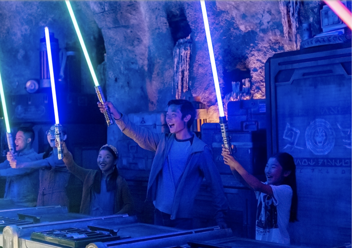 Young kids hold up custom lightsabers at Star Wars: Galaxy's Edge workshop at Disney's Hollywood Studios.