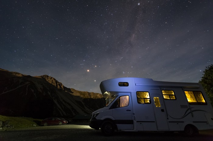 A camper van RV parks at night in a valley with the Milky Way visible above.