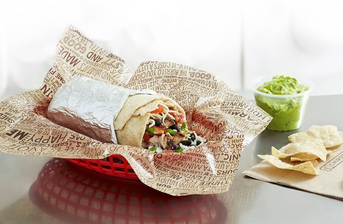 A basket with a tin foil-wrapped Chipotle burrito. Some tortilla chips and a cup of guacamole are off to the side.