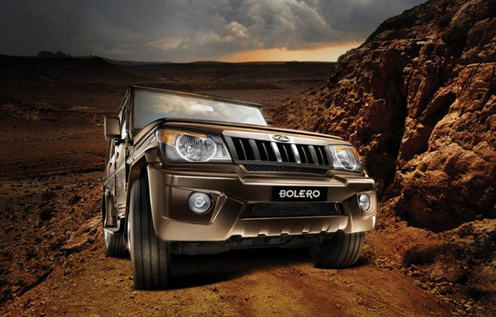 A brown Mahindra Bolero drives up a mountainous dirt road.