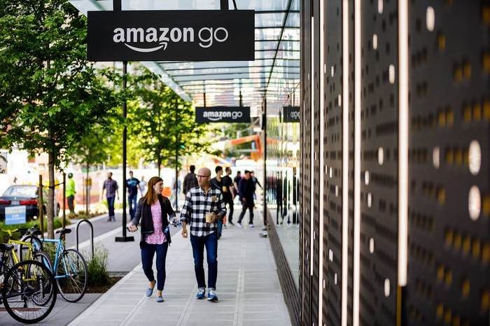 Two people walking on the sidewalk outside of an Amazon Go store.