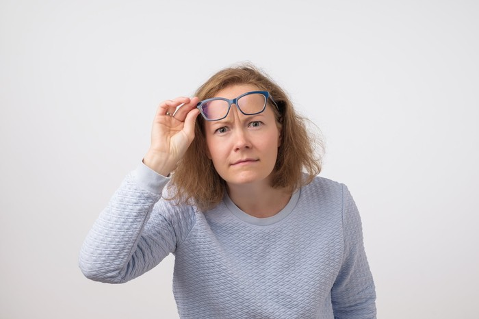 Woman removing glasses to look closely at something
