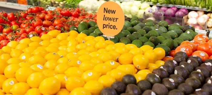 A grocery produce display with a sign saying New lower price.