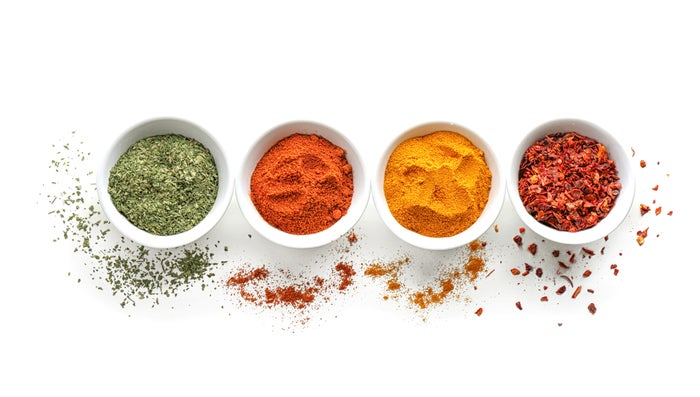 Four white bowls on a white background filled separately with oregano, paprika, turmeric, and red chili peppers