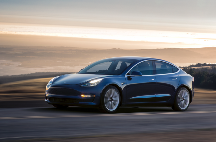 A blue Tesla Model 3 drives on a mountain road at dusk.