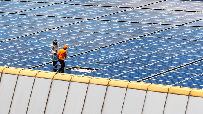 Workers installing a final solar panel on a large rooftop