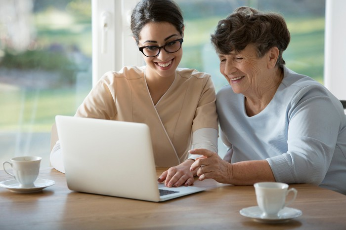 Smiling assistant sitting next to senior woman as they look at a laptop.