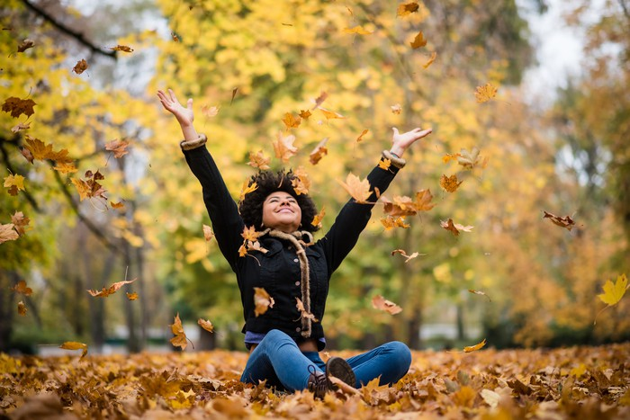A woman sits on ground covered in leaves and throws leaves up in the air in joy.
