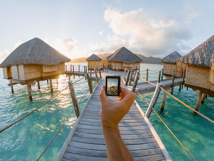 Hand holding out HERO 7 on a raised dock over the ocean with several cabanas in the background