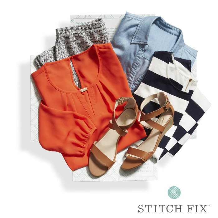 A sample of a Stitch Fix box that includes an orange top and brown sandals.