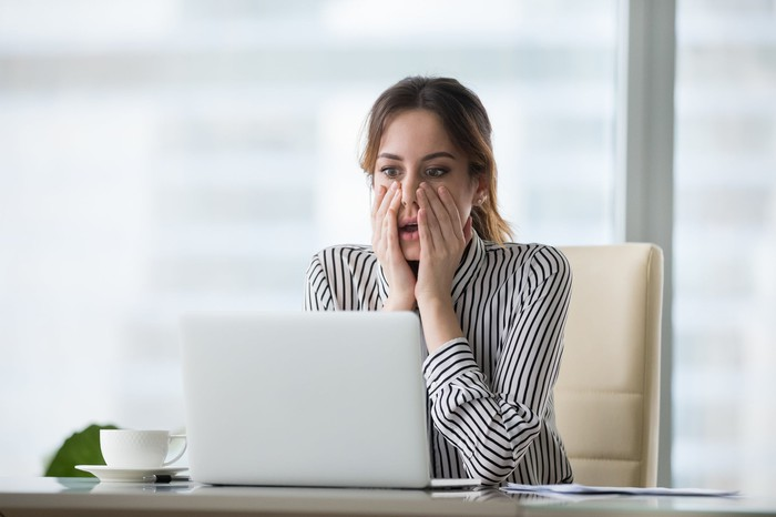 Professionally dressed woman sitting at laptop, holding her face as if shocked