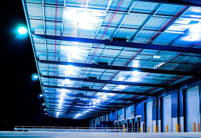 Docking bays of an industrial warehouse lit dramatically at night.