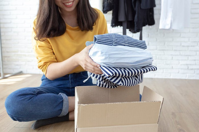 A woman unpacking clothes from a shipping box.