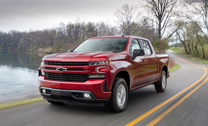 A red 2019 Chevrolet Silverado 1500, a light-duty full-size pickup truck, on a road near a lake.