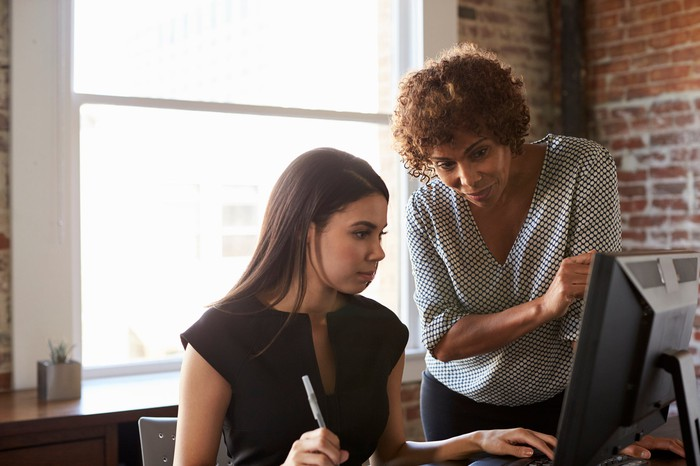 Older woman standing over younger woman at desk