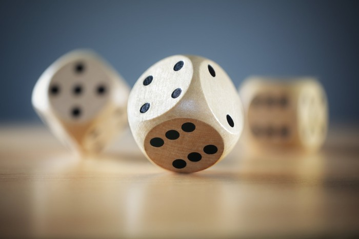 Wooden dice, one in foreground and two in a blurred background