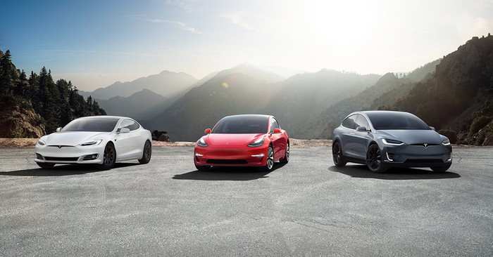 Tesla Model S, Model 3, and Model X lined up with mountains in the background.