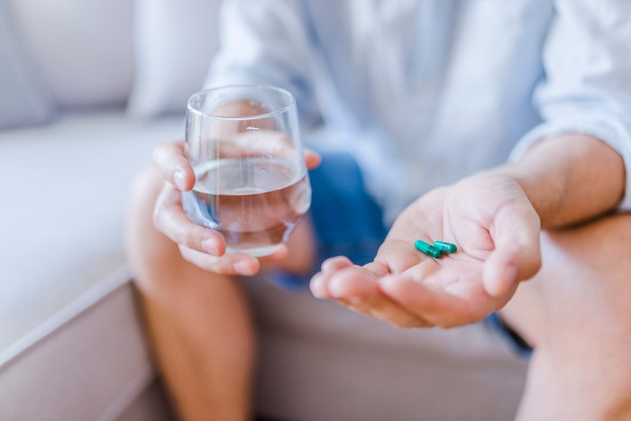 Man holding water glass in one hand and blue pills in the other hand
