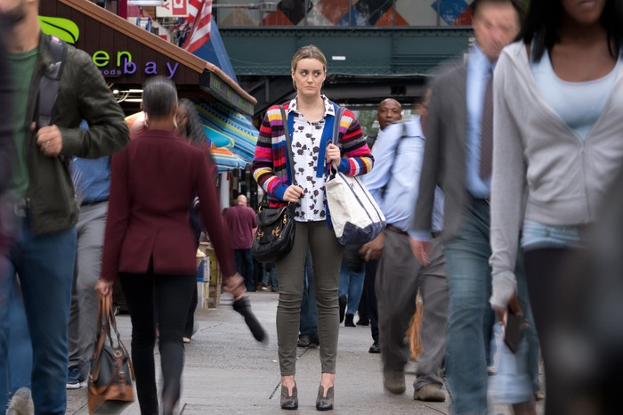 A woman with a apprehensive look standing on the sidewalk as throngs of people stream by her on both sides.