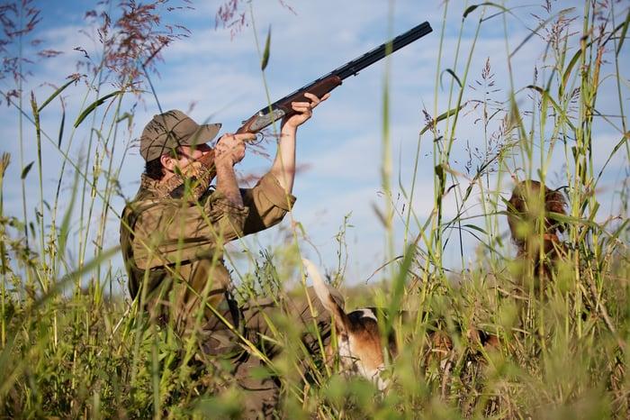 Hunter firing a shotgun