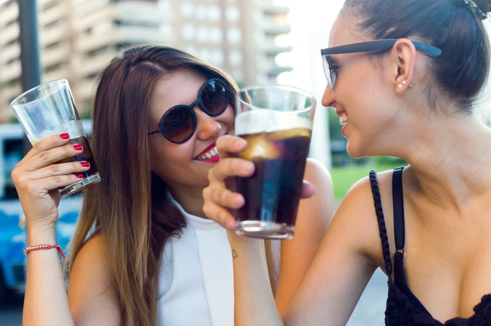 Two women drinking glasses of soda outside.