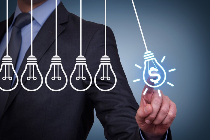 Businessman pointing to drawing of a light bulb with a dollar sign next to other light bulbs without dollar signs